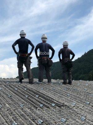 屋根の上で職人がポーズを決めています