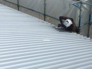屋根材をビス打ちしています
